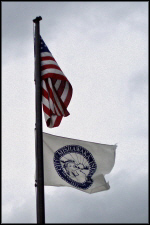 US flag above City of Mishawaka flag on flagpole on cloudy day